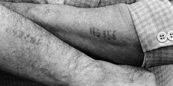 A Holocaust survivor displays the numerical tattoo stamped on his arm, a physical remnant of his imprisonment in a World War II Nazi concentration camp, during ceremonies commemorating the 50
