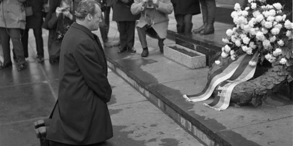 Zdjęcie archiwalne biało-czarne z 1970 roku, na którym kanclerz RFN Willy Brandt wykonuje symboliczny gest - klęka przed pomnikiem Bohaterów Getta w Warszawie, oddając hołd ofiarom Zagłady. F